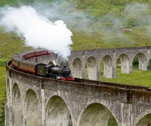 Steam train going over the curved Glenfinnan viaduct