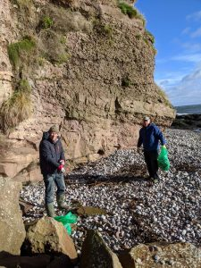 on Auchmithie beach with bags of rubbish from the beach clean
