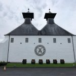 whitewashed Ardbeg distillery with logo on building