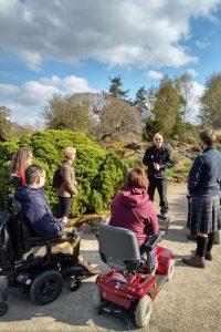 Guiding group in wheelchairs through botanic gardens in Edinburgh