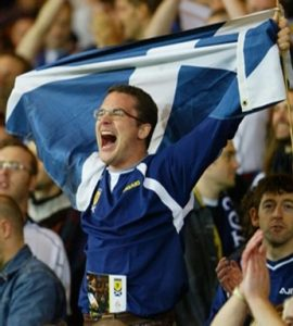 Scotland football fan in the crowds flying scotland flag to cheer on team